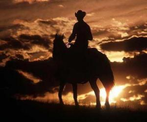 Puzle Cowboy ou vaqueiro cavalgando ao entardecer ou