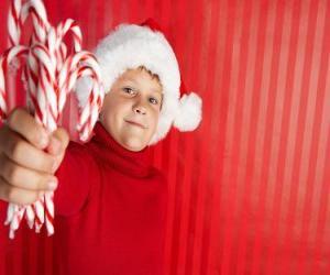 Puzle Criança com chapéu de Papai Noel e bastões de doces na mão