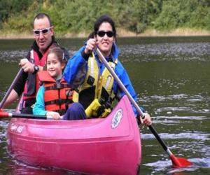 Puzle Família, pai, mãe e filha, vela e remando em uma canoa, equipados com coletes salva-vidas