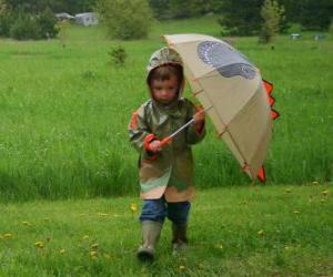 Puzle Menino com o guarda-chuva e capa de chuva sob a chuva da primavera
