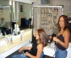 Cabeleireira penteando e secando o cabelo de uma cliente no salão de beleza