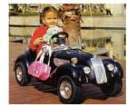 Menina em um carro de brinquedo clássico