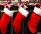 Meias de Natal decoradas penduradas na parede da chaminé