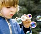Menina brincando a fazer bolhas de sabão