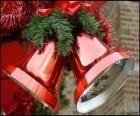 Sinos de Natal com um grande laço e folhas do abeto