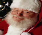 Feliz com seu chapéu de Papai Noel e barba branca