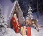 Papai Noel na porta de sua casa com uma rena e os presentes