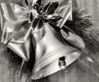 Sino de Natal decorado com folhas de azevinho e uma fita com um grande arco