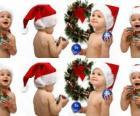 As crianças com chapéus de Papai Noel e brincar com as decorações de Natal