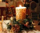 Vela acesa como um centro de mesa decorado com ramos de azevinho e pinheiro