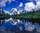 Um lago reflecte o escritório de montanha nas suas águas