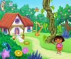 Dora, ao lado de uma casa na floresta