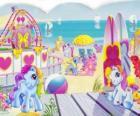 Vários pequenos pôneis na praia. My Little Pony