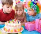 Menina no momento de soprar as velas do seu bolo de aniversário