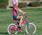 Menina andando de bicicleta no parque na primavera