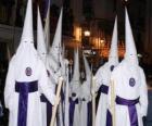 Nazarenos ou penitentes numa procissão durante a Semana Santa com capuz ou cone, manto e capa
