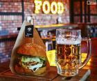 Um hamburguer completo e um jarro é cerveja bem refrigeração