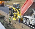 Dos trabalhadores que trabalham em uma rodovia