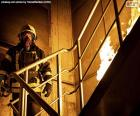 Bombeiro em uma escada em chamas