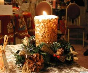 Puzle Vela acesa como um centro de mesa decorado com ramos de azevinho e pinheiro